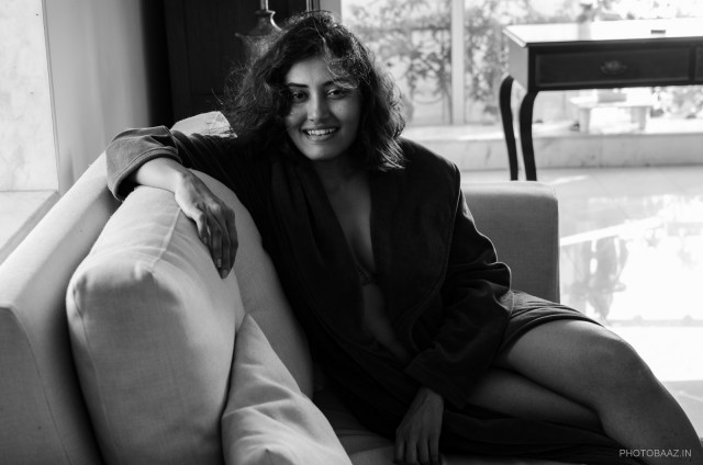Nivedita Pohankar sitting on a sofa smiling at the camera with her hair blowing.