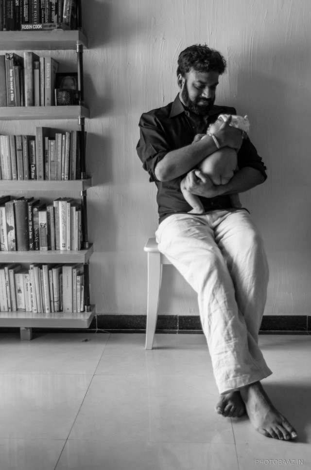 Father with his infant son sitting on a stool next to a shelf full of books.
